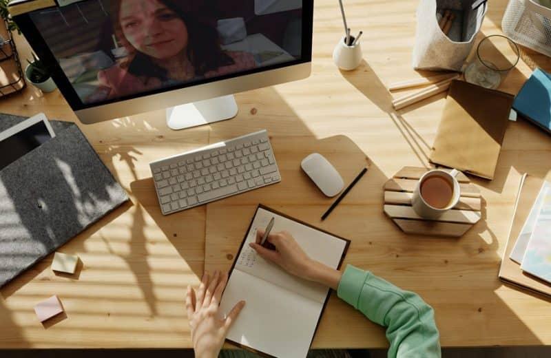 Une femme écrit devant son PC